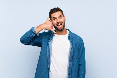 Handsome man over isolated blue background making phone gesture. Call me back sign Фото со стока