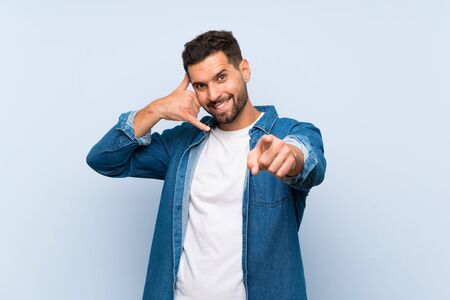 Handsome man over isolated blue background making phone gesture and pointing front Фото со стока