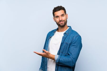 Handsome man over isolated blue background presenting an idea while looking smiling towards