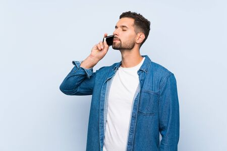 Handsome man over isolated blue background keeping a conversation with the mobile phone