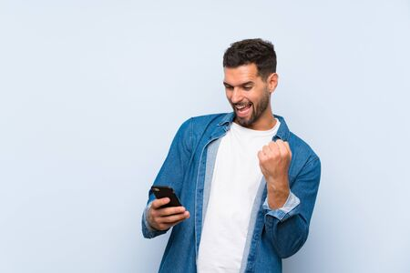 Handsome man over isolated blue background with phone in victory position Фото со стока - 132028116