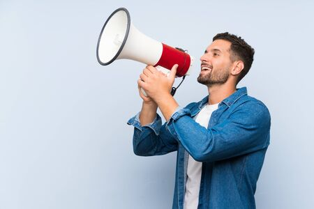 Handsome man over isolated blue background shouting through a megaphone