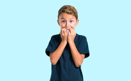 El niño está un poco nervioso y asustado sobre fondo azul.
