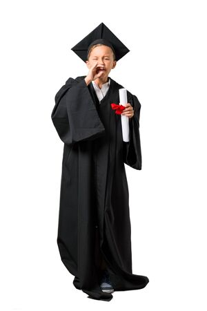 Full body of Little boy graduating shouting with mouth wide open on isolated white background