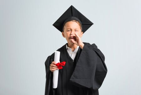 Little boy graduating shouting with mouth wide open on grey background