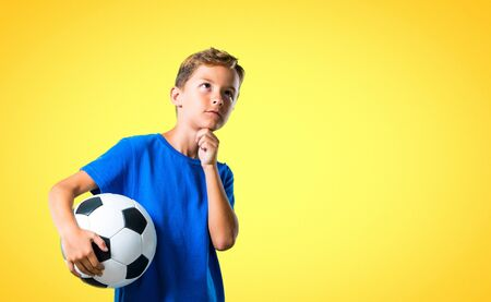 Boy playing soccer and thinking on yellow background