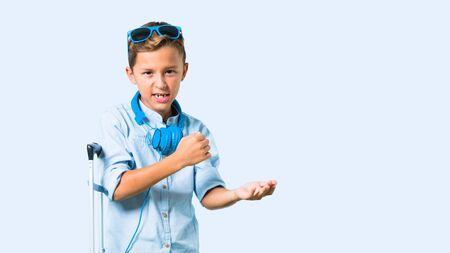 Kid with sunglasses and headphones traveling with his suitcase unhappy and frustrated with something. Negative facial expression on blue background