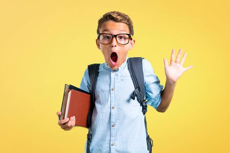 Student boy with backpack and glasses with surprise and shocked facial expression on yellow background