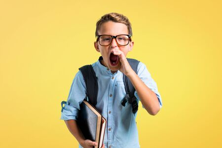 Student boy with backpack and glasses shouting with mouth wide open on yellow background