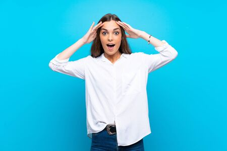 Young woman over isolated blue background with surprise expression Stok Fotoğraf