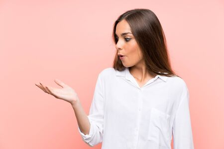 Young woman over isolated pink background holding copyspace imaginary on the palm