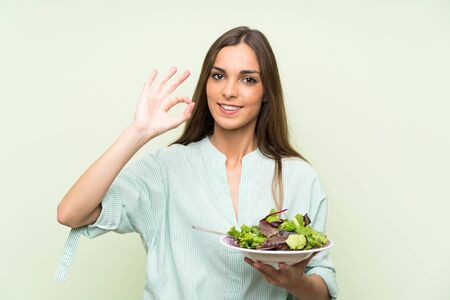 Young woman with salad over isolated green wall showing ok sign with fingers