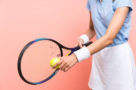 Young tennis player woman over isolated pink wall