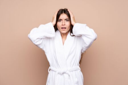 Young girl in a bathrobe over isolated background with surprise facial expression