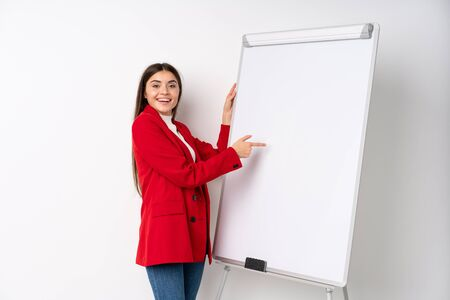 Young woman giving a presentation on white board giving a presentation on white board and writing in it