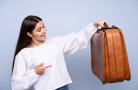 Young woman over isolated blue background holding a vintage briefcase