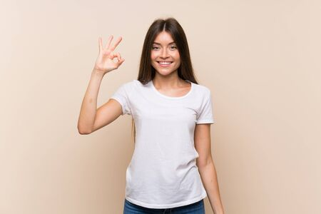 Pretty young girl over isolated background showing ok sign with fingers