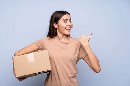 Young woman over isolated blue background holding a box to move it to another site and pointing side
