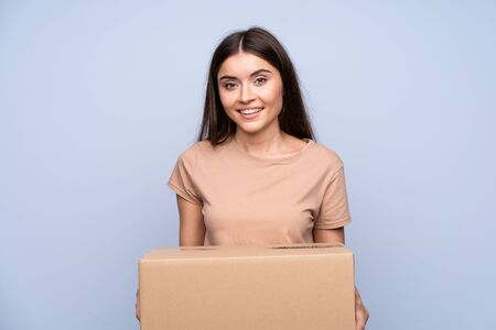 Young woman over isolated blue background holding a box to move it to another site