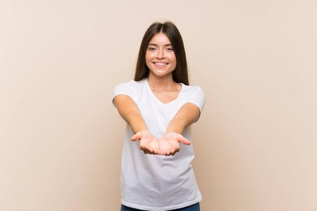 Pretty young girl over isolated background holding copyspace imaginary on the palm to insert an ad