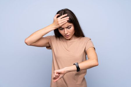 Young woman over isolated blue background with wrist watch and surprised
