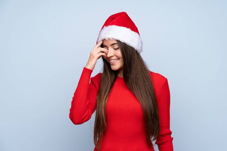 Girl with christmas hat over isolated blue background laughing