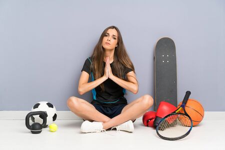 Young sport woman sitting on the floor pleading