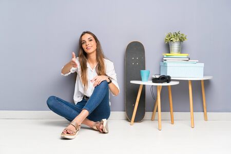 Young woman sitting on the floor handshaking after good deal Stock Photo