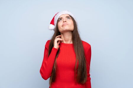Girl with christmas hat over isolated blue background thinking an idea