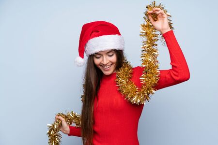 Girl with christmas hat over isolated blue background Stock Photo