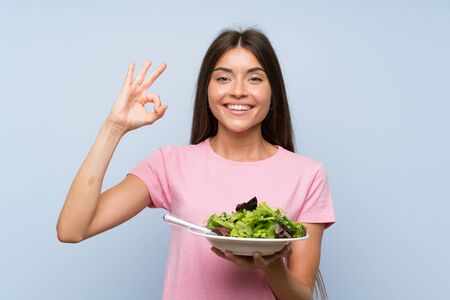 Young woman with salad over isolated blue background showing ok sign with fingers