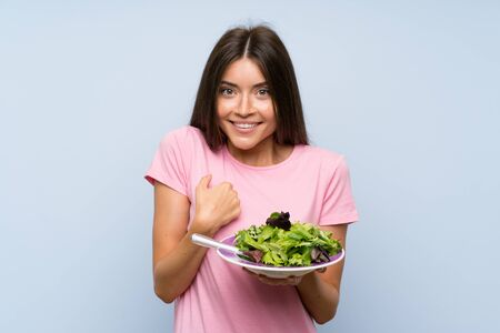 Young woman with salad over isolated blue background with surprise facial expression