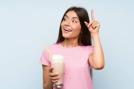 Young woman with strawberry milkshake over isolated blue background intending to realizes the solution while lifting a finger up Archivio Fotografico