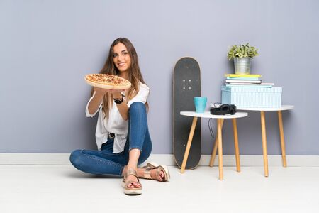 Young woman sitting on the floor with a pizza