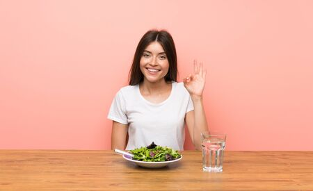 Young woman with a salad showing ok sign with fingers