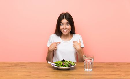Young woman with a salad with surprise facial expression