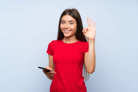 Brunette young woman with a mobile phone over isolated blue wall showing ok sign with fingers