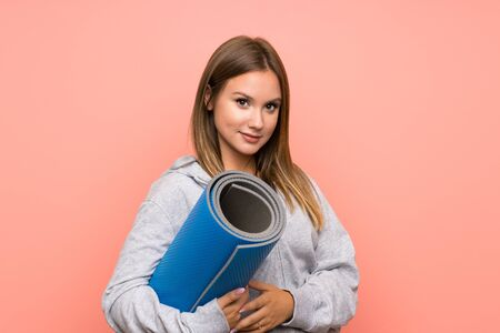 Teenager sport girl with mat over isolated pink background