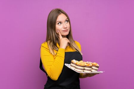 Teenager girl holding lots of different mini cakes over isolated purple background thinking an idea