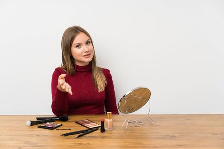 Teenager girl with makeup palette and cosmetics in a table handshaking after good deal
