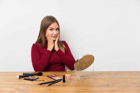 Teenager girl with makeup palette and cosmetics in a table with surprise facial expression