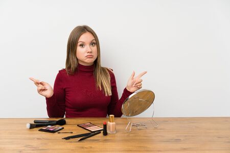 Teenager girl with makeup palette and cosmetics in a table pointing to the laterals having doubts