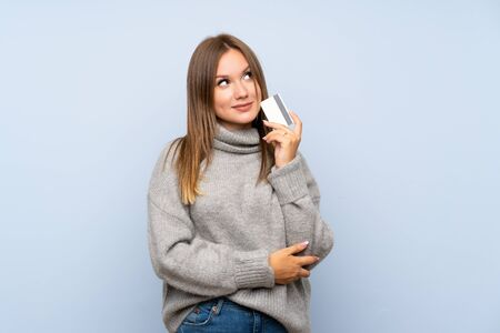 Teenager girl with sweater over isolated blue background holding a credit card