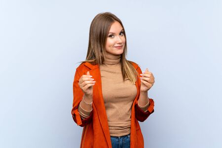 Teenager girl with coat over isolated blue background making money gesture Zdjęcie Seryjne
