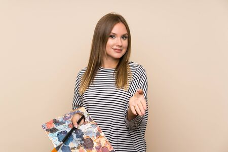 Teenager girl holding a palette over isolated background handshaking after good deal Zdjęcie Seryjne