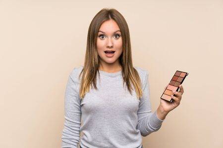 Teenager girl with makeup palette over isolated background with surprise and shocked facial expression