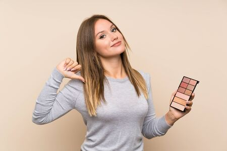 Teenager girl with makeup palette over isolated background proud and self-satisfied Foto de archivo