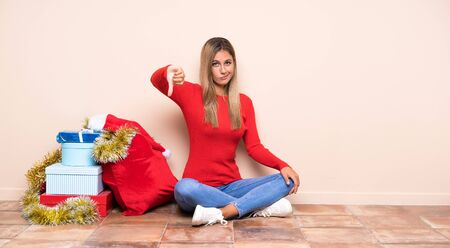 Girl in christmas holidays sitting on the floor showing thumb down sign Stock Photo