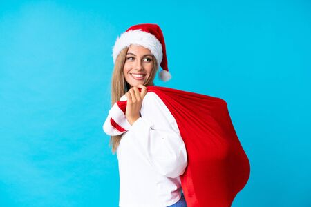 Young blonde woman picking up a bag full of presents over isolated background Stock Photo