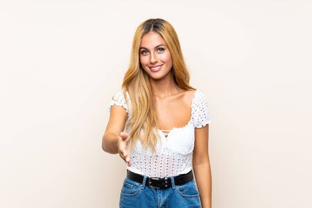 Young blonde woman over isolated background handshaking after good deal